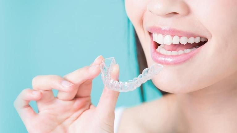 Woman putting in clear Invisalign aligner l Dentist 10011